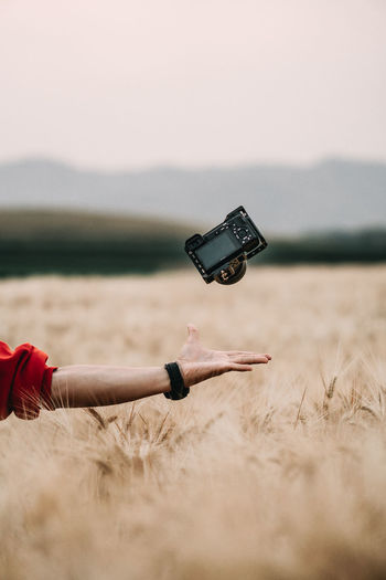 Cropped image of hand with camera over wheat field