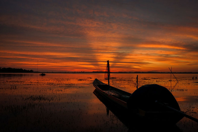 Silhouette boat moored in lake against sky during sunset