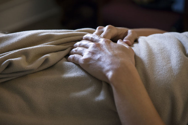 Midsection of man lying on bed at spa