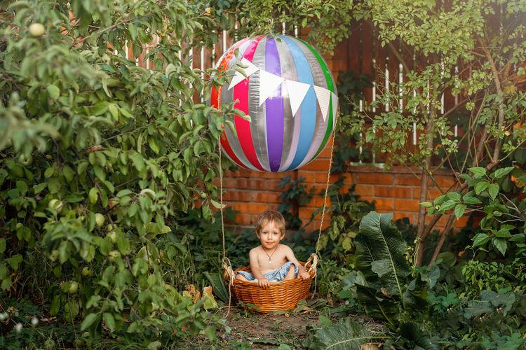 Boy wearing mask in basket at yard