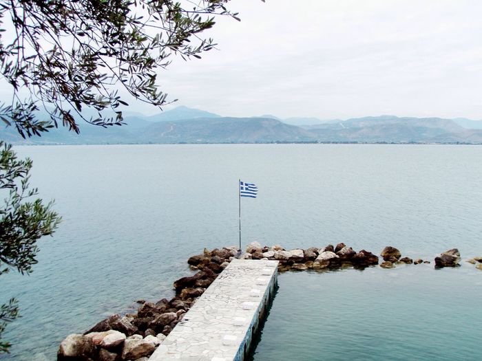 Flag At Jetty Against Calm Sea