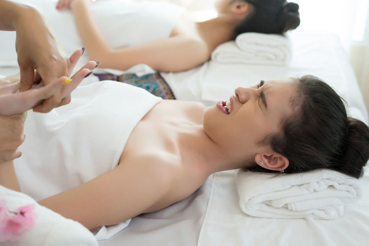 Cropped Hands Of Massage Therapist Massaging Young Woman In Spa