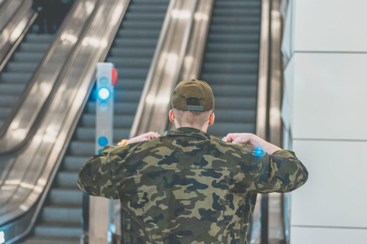 Rear View Of Man In Camouflage Jacket Standing Against Escalator At Railroad Station