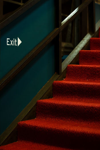 Close-up of exit sign on red staircase