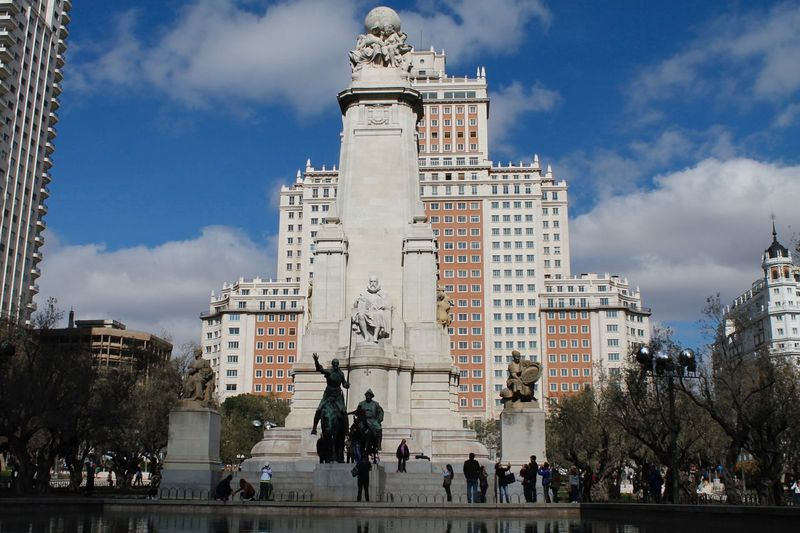 People at miguel de cervantes monument in plaza de espana against edificio espana