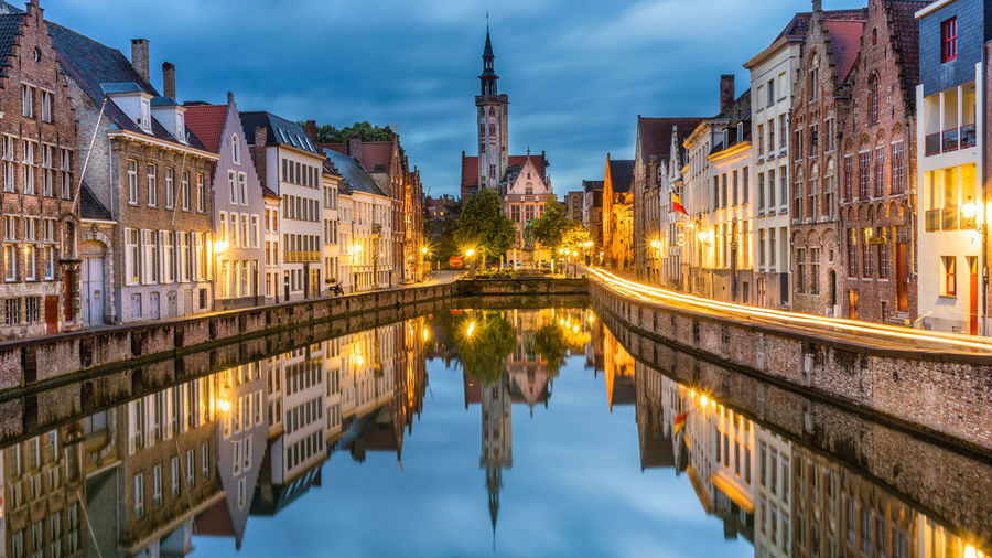 Reflection of buildings in canal at dusk