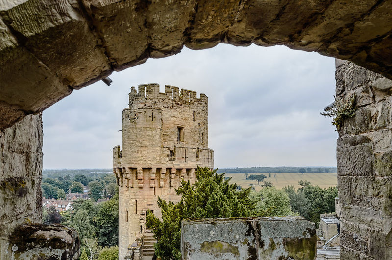 Tower framed by a stone arch in the Castle of Warwick Ancient Ancient Civilization Arch Architecture Built Structure Castle Cloud Cloud - Sky Day Deterioration Fortress History Nature No People Old Old Ruin Outdoors Ruined Sky Stone Material Stone Wall The Past Tourism Travel Destinations Warwick