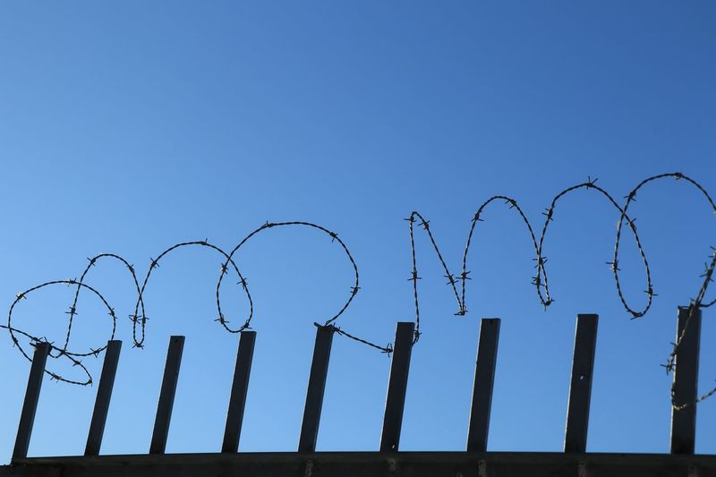 Low angle view of barbed wire against clear blue sky