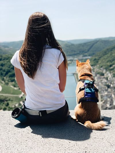 Rear view of woman with dog sitting outdoors