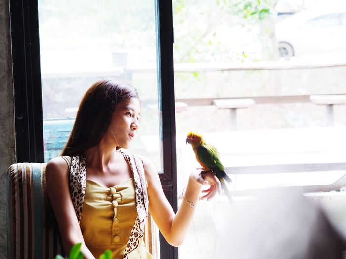 Sun cornure Parrot on the hands of the girl EyeEm Selects Animal Wildlife Alone In Nature Animals In The Wild Garden Animals Blur Background Spring Bird Sunconure Parrot Colors Cople Sad & Lonely Alone Time Vintage Style Beautiful Woman Beutyful Girl Beuty Of Nature Eating Young Women Holding Window Women Smelling Autumn Mood