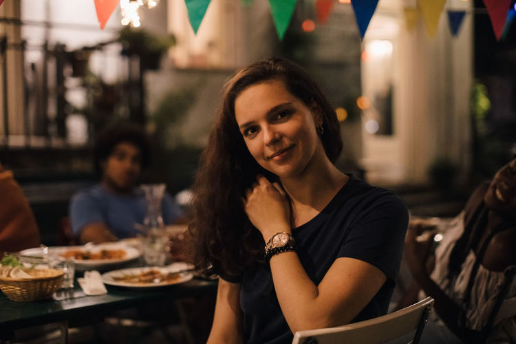 Portrait of smiling young woman sitting at restaurant