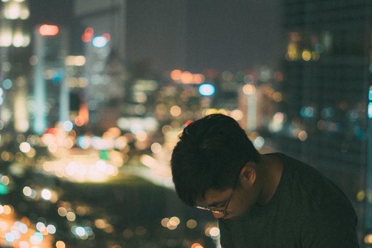 Portrait of man in illuminated city at night