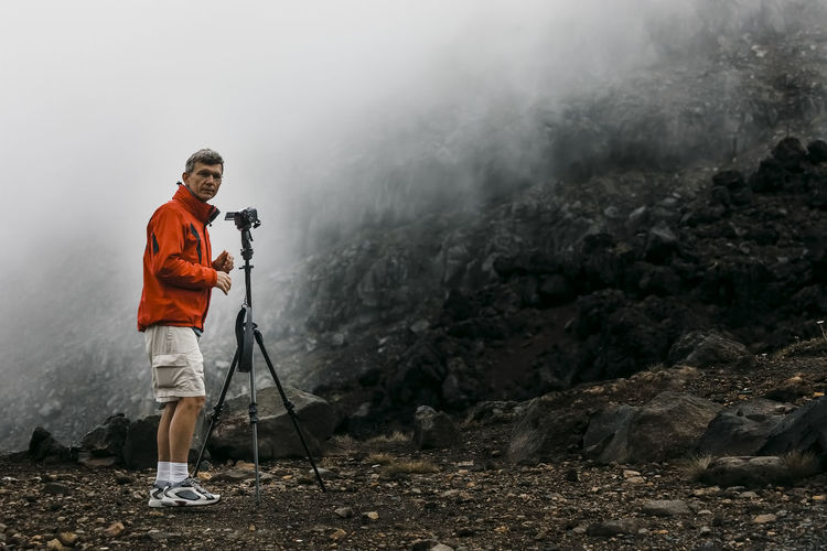 Portrait of man with camera and tripod standing against mountain during foggy weather