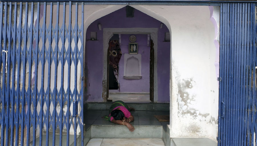 Woman leaning on door of building