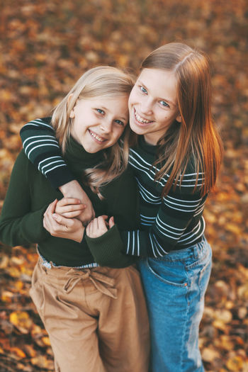 Two happy little girls sisters laughing, having fun and playing in the fall in nature outdoors