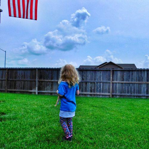 Rear View Of Girl Walking On Grassy Field Against Sky