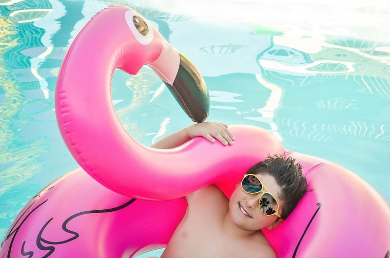 Flamingo Pink Sunglasses Reflection Palm Trees Stylish Boy Boy With Sunglasses Flamingo Floatie Childhood Boy Swimming Pool Looking At Camera Smiling One Person Portrait Water Pink Color Swimming Leisure Activity Vacations Childhood Fun Summer Cheerful Day Happiness Real People Flamingo Outdoors EyeEmNewHere