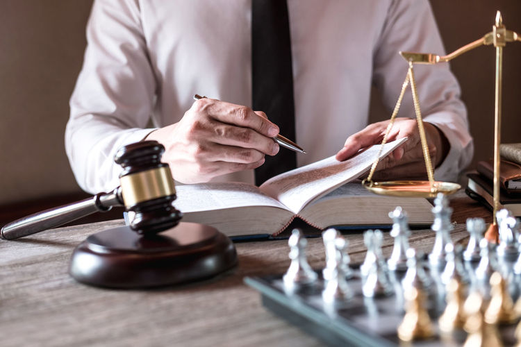 Midsection of judge writing in book on table