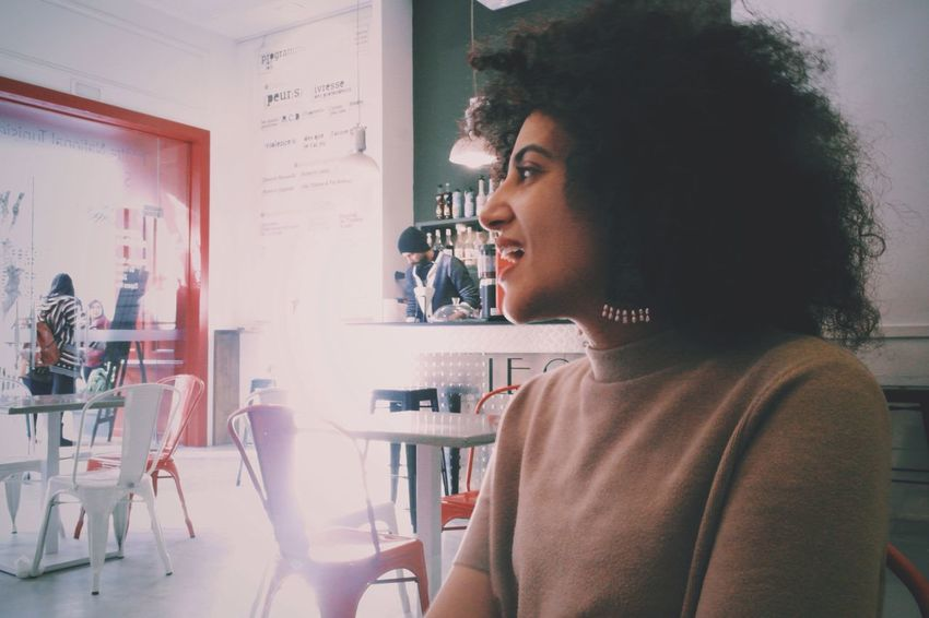 Young Adult Real People Indoors  One Person Young Women Casual Clothing Beautiful Woman Leisure Activity Side View Lifestyles Sitting Curly Hair Women Day Adult People Lights Laughing Red