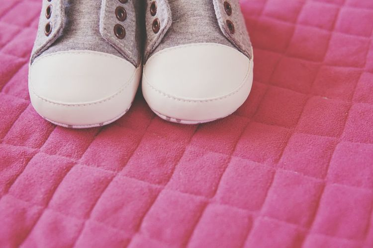 Low section of kid shoes on pink background