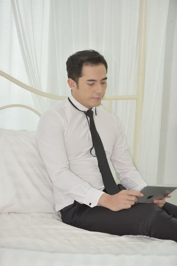 One Person Wireless Technology Sitting Bed Furniture Technology Communication Young Adult Indoors  Three Quarter Length Curtain Lifestyles Real People Connection Young Men Leisure Activity Looking Men