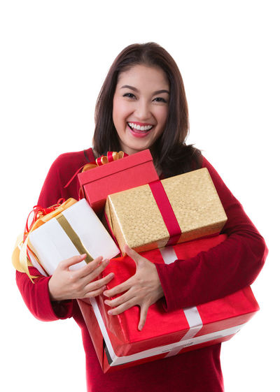 Merry Christmas Adult Adults Only Black Hair Casual Clothing Cheerful Christmas Gift Happiness Holding Looking At Camera One Person One Woman Only One Young Woman Only Only Women People Portrait Red Smiling Standing Studio Shot Toothy Smile Waist Up Women Young Adult Young Women