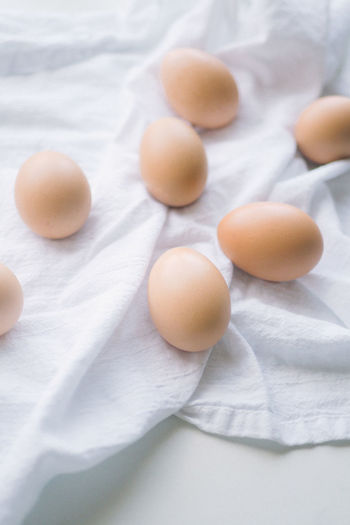 Brown eggs on a white kitchen towel