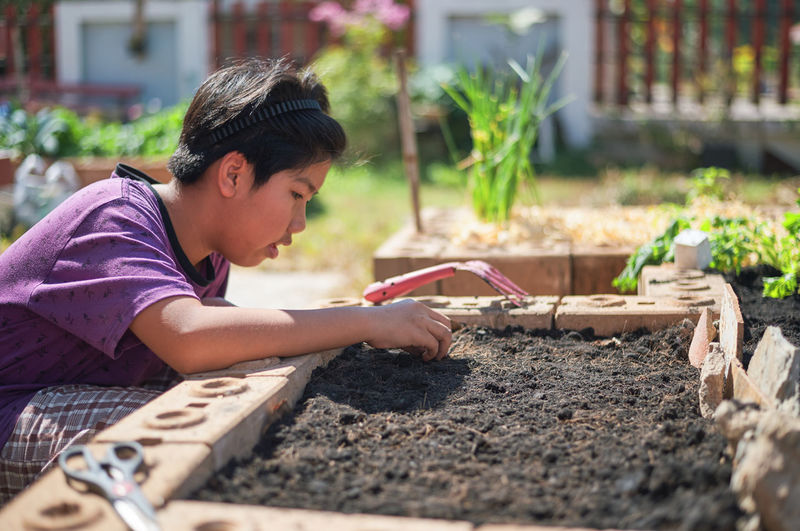 Side view of boy gardening outdoors