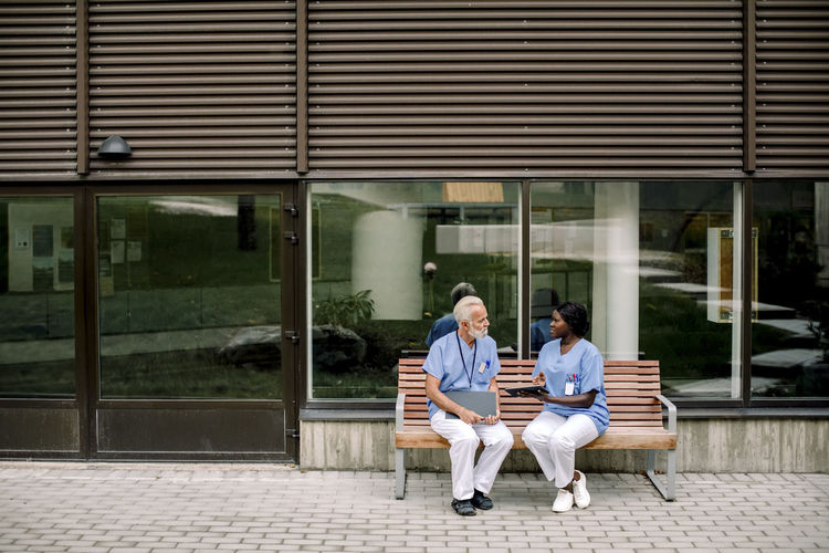 People sitting on bench against building