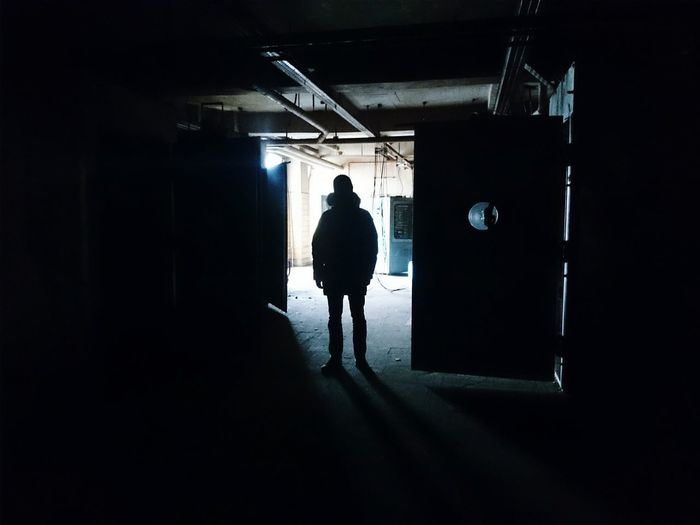 Silhouette of man standing in dark building