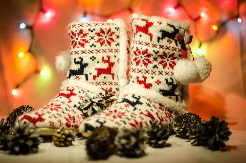 Close-up of christmas socks and pine cones with illuminated lights in background