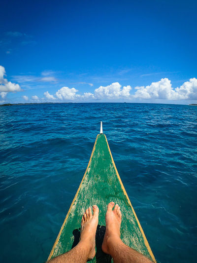 Low section of man sitting on boat in sea against blue sky