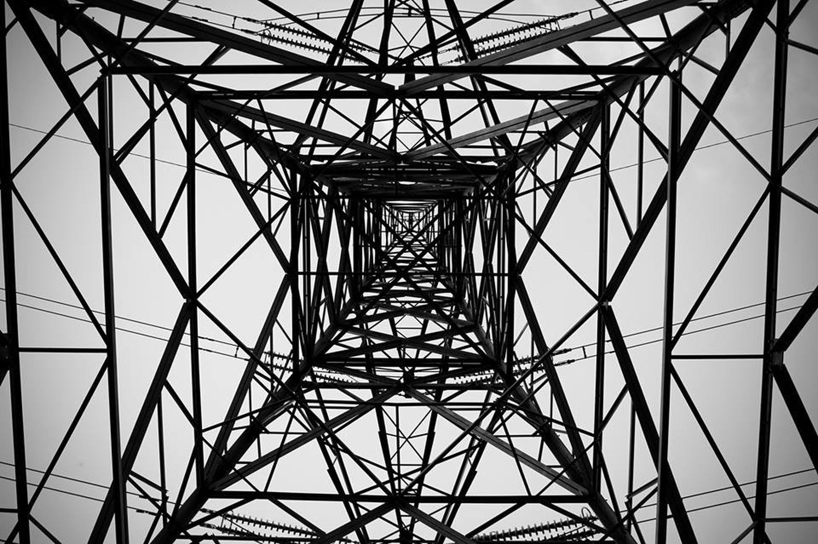 low angle view, electricity pylon, backgrounds, full frame, built structure, connection, power line, sky, metal, pattern, power supply, architecture, electricity, grid, complexity, fuel and power generation, ceiling, directly below, no people, day