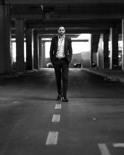 Portrait of man walking on road in parking lot