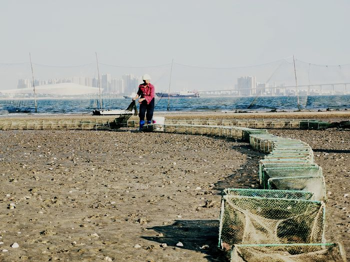 Man working with fishing net on sea shore against sky