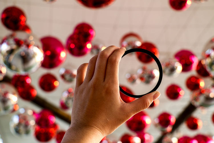 Cropped image of woman holding bangle against ceiling