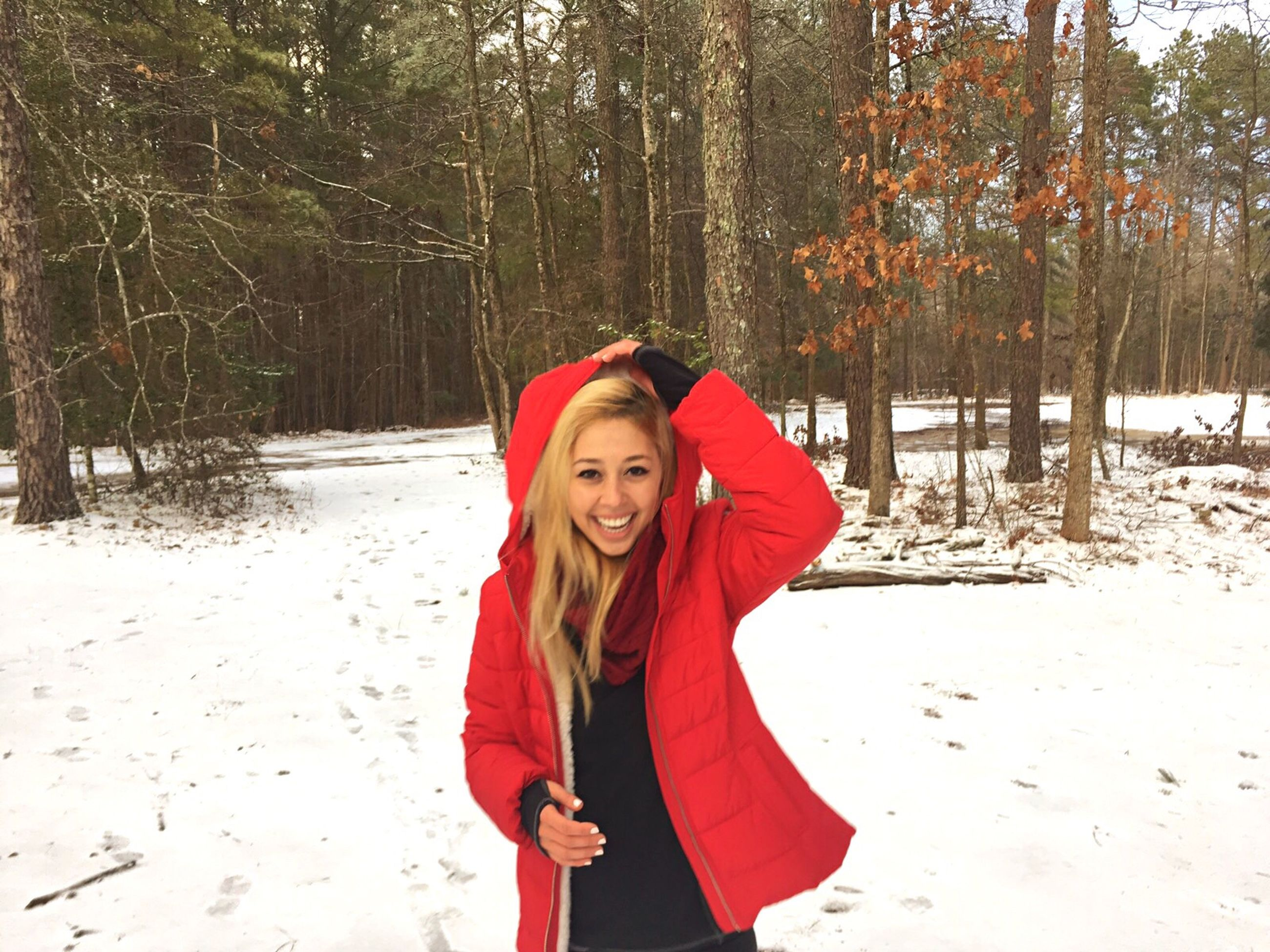 snow, portrait, winter, cold temperature, vitality, young adult, smiling, one woman only, looking at camera, tree, confidence, only women, red, warm clothing, beauty, beautiful woman, blond hair, front view, long hair, one young woman only, one person, young women, leisure activity, happiness, adults only, people, standing, adult, cheerful, women, day, outdoors, nature, beauty in nature