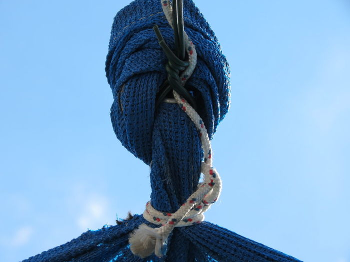 Low angle view of rope tied up against blue sky
