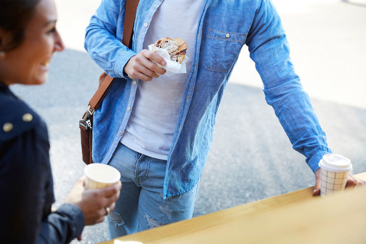 Midsection of couple holding coffee