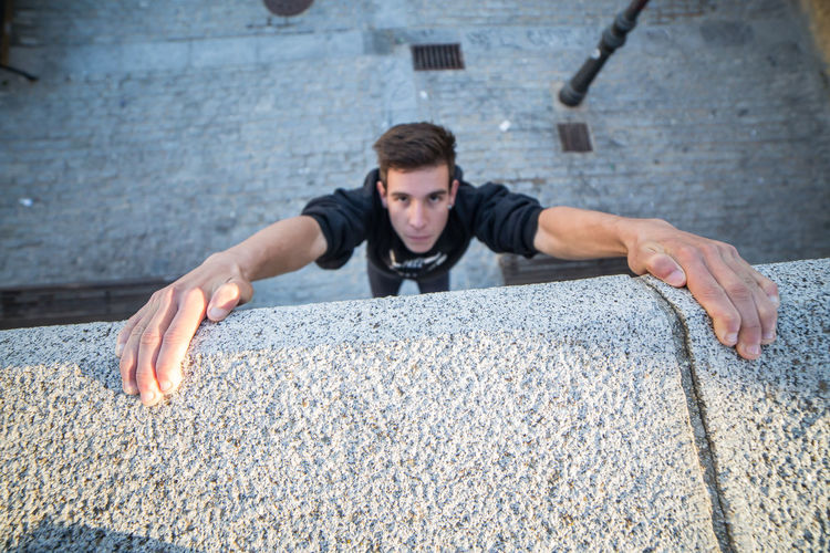 Portrait of young man climbing on concrete wall