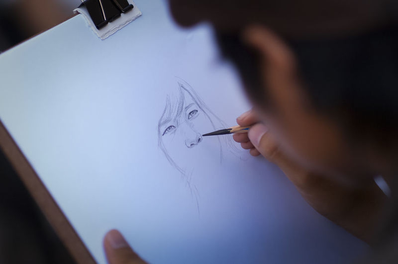 Close-Up Of Person Making Sketch On Paper