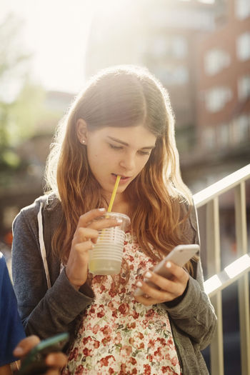 Close-up of a young woman drinking water from mobile phone outdoors