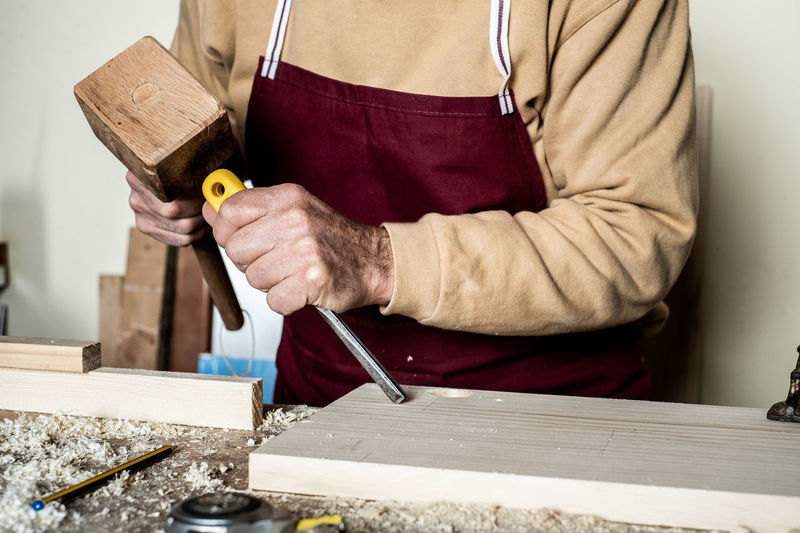 Midsection of carpenter working on wood