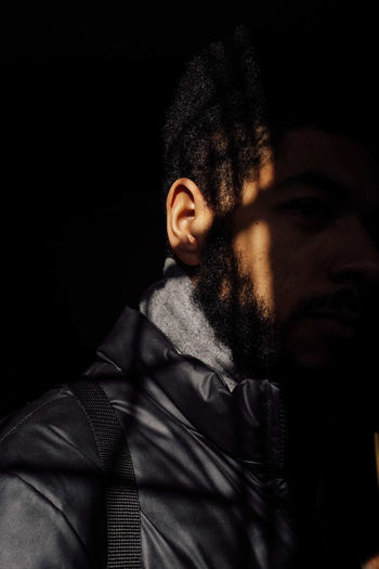One Person Young Adult Clothing Portrait Headshot Warm Clothing Indoors  Jacket Black Background Looking Lifestyles Real People Young Men Adult Looking Away Front View Winter Serious Contemplation Scarf Dark