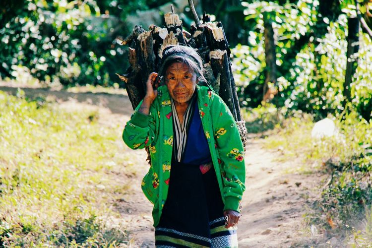 One Person Green Color Plant Adult Nature Front View Day Lifestyles Outdoors Real People Sunlight Standing Land Growth Waist Up Landscape Women Clothing Hairstyle Traditional Clothing Looking At Camera Travel Destinations Chin State, Myanmar Myanmar The Portraitist - 2019 EyeEm Awards