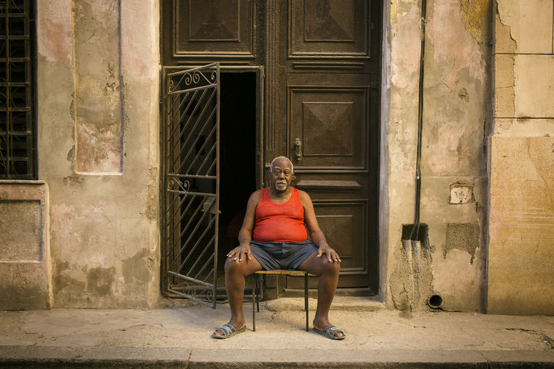 Portrait of man sitting on seat against building