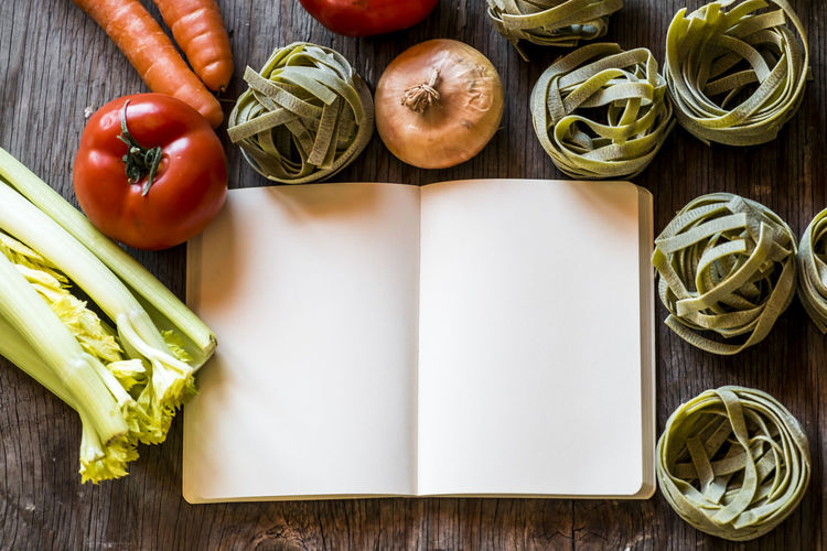 High angle view of raw food and blank book on table