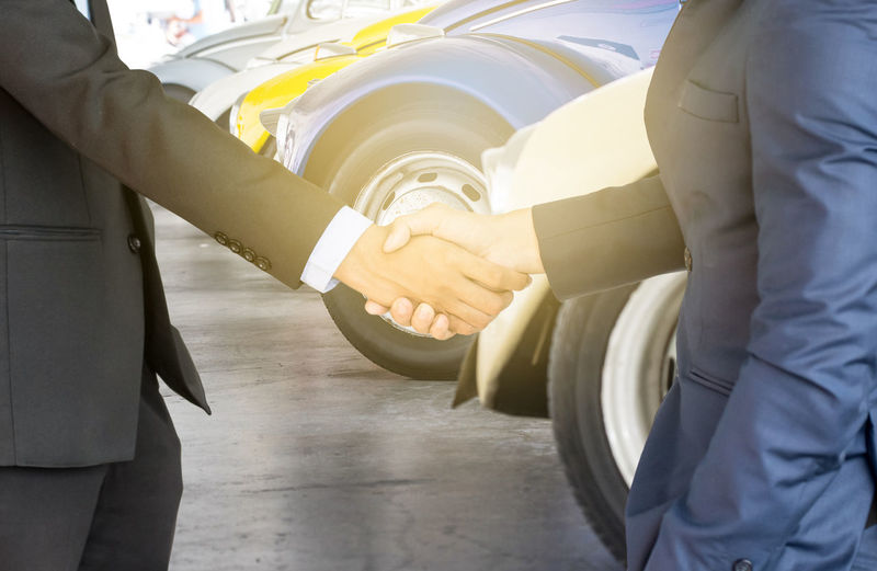 Midsection Of Businessmen Shaking Hands Outdoors