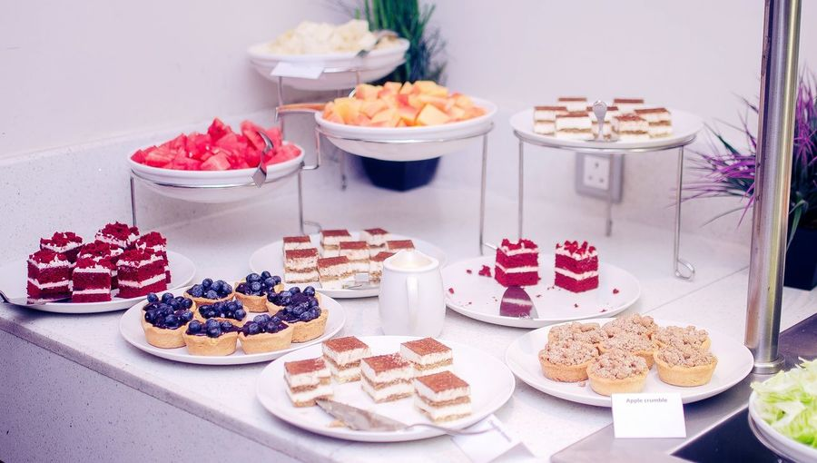 Cakes And Fruits Slices With Tarts Arranged On Table