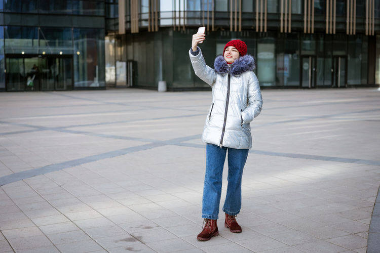 Young woman in a warm jacket communicates online by phone on the street